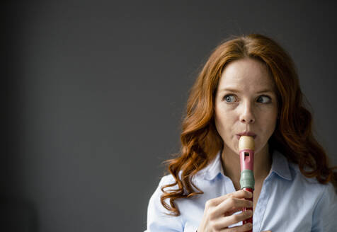 Portrait of redheaded woman playing recorder - KNSF06444