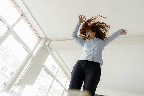 Redheaded woman standing on desk in a loft moving and screaming - KNSF06450