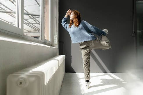 Redheaded woman standing on one leg in a loft looking out of window - KNSF06453