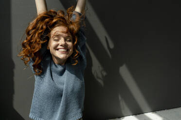 Portrait of happy redheaded woman with eyes closed raising hands - KNSF06459