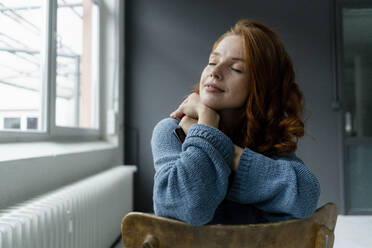 Portrait of redheaded woman with digital tablet relaxing in a loft - KNSF06471