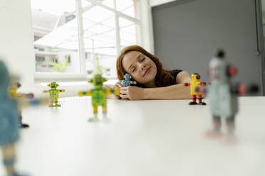 Portrait of redheaded businesswoman in a loft with miniature robots on desk - KNSF06477
