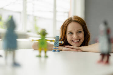 Portrait of smiling redheaded businesswoman in a loft with miniature robots on desk - KNSF06480