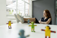 Portrait of redheaded woman in a loft with miniature robots on desk - KNSF06483