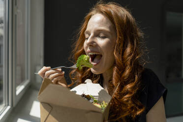 Portrait of redheaded businesswoman in a loft eating healthy takeaway food - KNSF06486