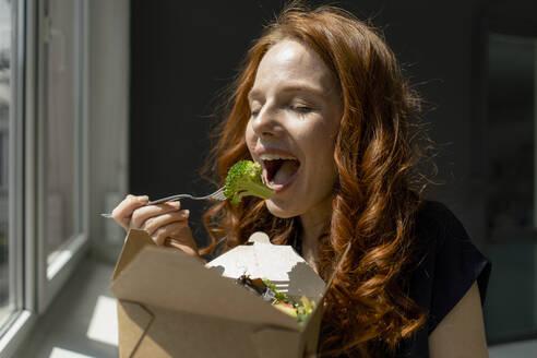 Portrait of redheaded businesswoman in a loft eating healthy takeaway food - KNSF06486