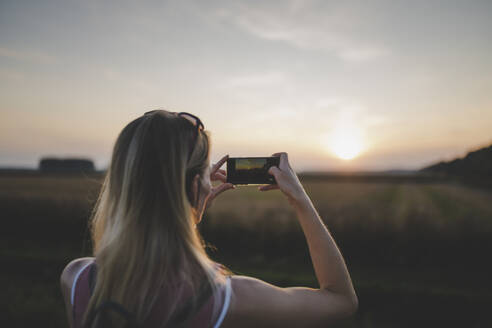 Woman taking a photo of sunset with her smartphone - CHPF00572