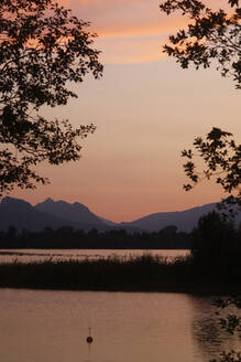 Scenic view of Forggensee lake and silhouette mountains against sky during sunset at Ostallgäu, Germany - JTF01299