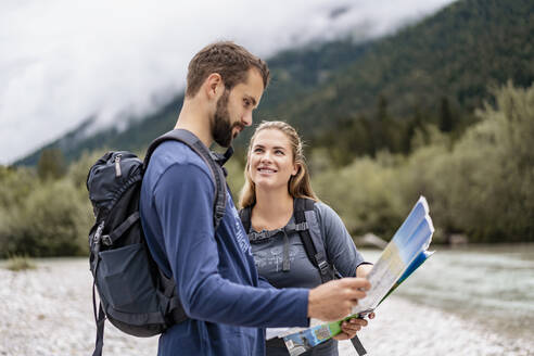 Young couple on a hiking trip reading map, Vorderriss, Bavaria, Germany - DIGF08254