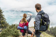 Young couple on a hiking trip in the mountains looking at view, Herzogstand, Bavaria, Germany - DIGF08269