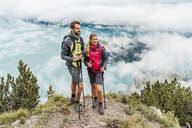 Confident young couple on a hiking trip in the mountains, Herzogstand, Bavaria, Germany - DIGF08272