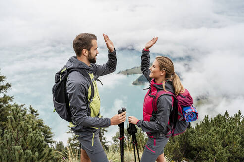 Happy young couple on a hiking trip in the mountains high fiving, Herzogstand, Bavaria, Germany - DIGF08275