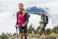Confident young couple on a hiking trip in the mountains, Herzogstand, Bavaria, Germany - DIGF08281