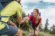 Young man helping girlfriend on a hiking trip in the mountains, Herzogstand, Bavaria, Germany - DIGF08296