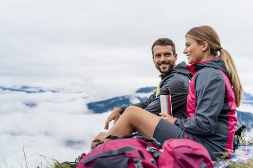 Young couple on a hiking trip in the mountains having a break, Herzogstand, Bavaria, Germany - DIGF08305
