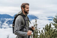 Confident young man on a hiking trip in the mountains, Herzogstand, Bavaria, Germany - DIGF08314