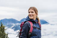 Smiling young woman on a hiking trip in the mountains, Herzogstand, Bavaria, Germany - DIGF08317