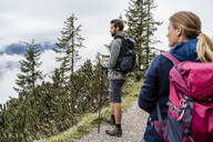 Young couple on a hiking trip in the mountains looking at view, Herzogstand, Bavaria, Germany - DIGF08320