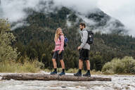 Young couple on a hiking trip crossing river on a log, Vorderriss, Bavaria, Germany - DIGF08326
