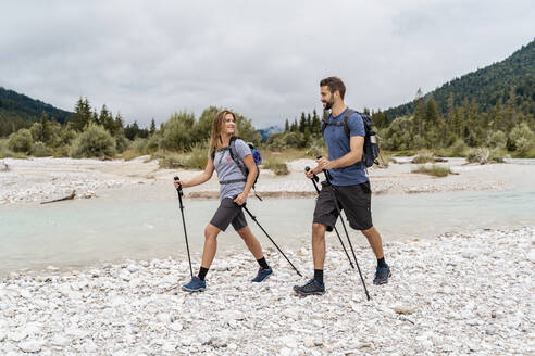 Young couple on a hiking trip at riverside, Vorderriss, Bavaria, Germany - DIGF08338