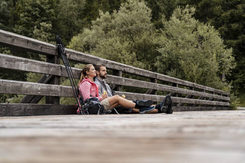 Young couple having a break on a wooden bridge during a hiking trip, Vorderriss, Bavaria, Germany - DIGF08353