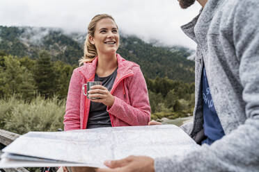 Young woman with drink smiling at man during a hiking trip, Vorderriss, Bavaria, Germany - DIGF08359