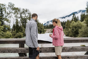 Young couple on a hiking trip reading map on wooden bridge, Vorderriss, Bavaria, Germany - DIGF08362