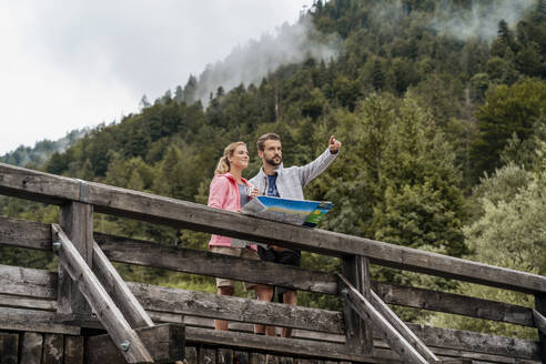 Young couple on a hiking trip with map on wooden bridge, Vorderriss, Bavaria, Germany - DIGF08365