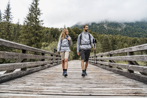 Young couple on a hiking trip walking on wooden bridge, Vorderriss, Bavaria, Germany - DIGF08368