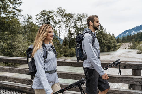Confident young couple on a hiking trip walking on wooden bridge, Vorderriss, Bavaria, Germany - DIGF08371