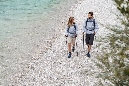 Young couple on a hiking trip walking at the riverside, Vorderriss, Bavaria, Germany - DIGF08374