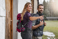 Young couple at a farmhouse during a hiking trip, Vorderriss, Bavaria, Germany - DIGF08377