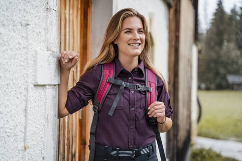 Smiling young woman at a farmhouse during a hiking trip, Vorderriss, Bavaria, Germany - DIGF08380