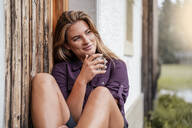 Young woman having a drink at a farmhouse during a hiking trip, Vorderriss, Bavaria, Germany - DIGF08386