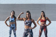 Portrait of confident young woman with friends  flexing muscles - JCMF00201