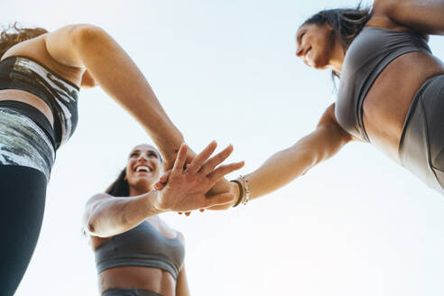 Three happy sporty women stacking their hands after doing sports - JCMF00204