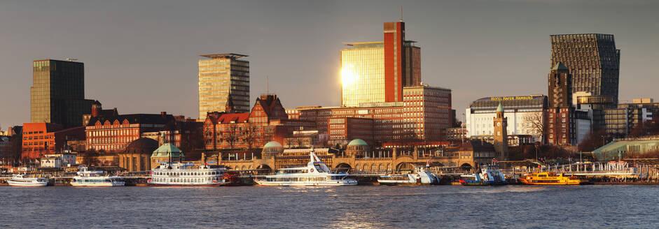 View from Elbe River to St. Pauli Landungsbruecken pier and skyscraper Tanzende Tuerme at sunset, St. Pauli, Hamburg, Europe - RHPLF08792
