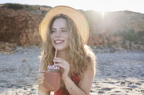 Happy young woman with a smoothie on the beach - IGGF01312