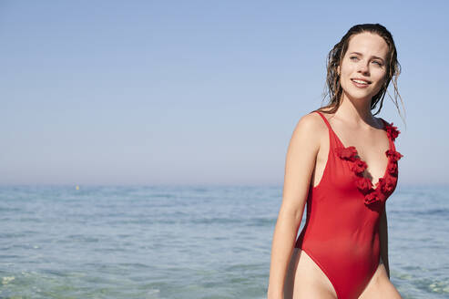 Portrait of young woman in red swimsuit at the sea - IGGF01324