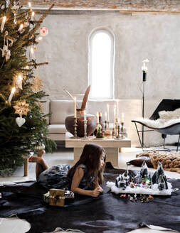 Girl lying by nativity scene and Christmas tree in living room - FOLF11154