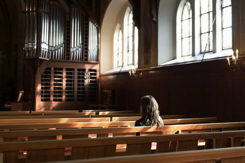 Priest sitting on pew in church - FOLF11235