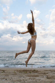 Young woman jumping for joy on the beach - AFVF03890