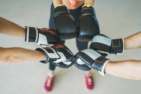Close-up of training partners with boxing gloves in gym - DLTSF00080
