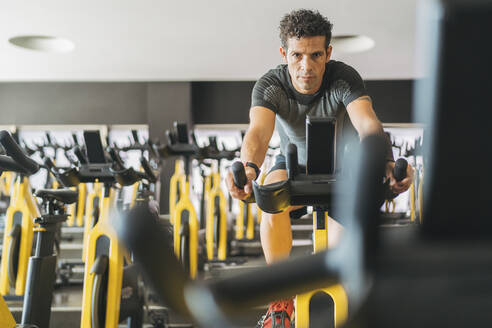 Portrait of man in spinning class in gym - DLTSF00086