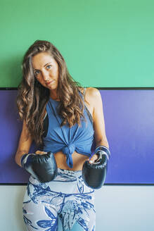 Portrait of woman with boxing gloves in gym - DLTSF00089