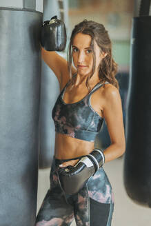 Portrait of woman with boxing gloves at sandbag in gym - DLTSF00092