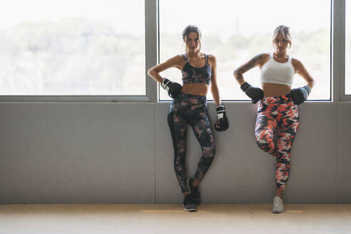 Portrait of two women with boxing gloves at the window in gym - DLTSF00098