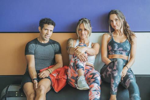 Portrait of three athletes having a break in gym - DLTSF00104