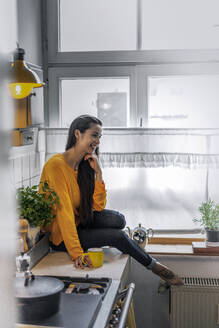 Happy young woman sitting on kitchen counter at home - RIBF00984