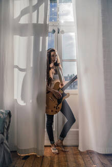 Serious young woman standing at the window at home with a guitar - RIBF01020